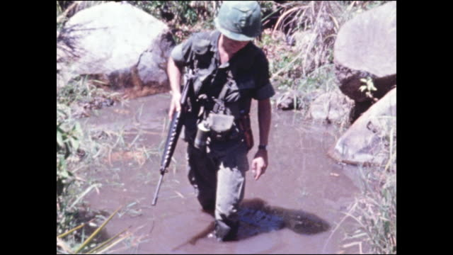 173rd airborne soldiers standing amid high grass waiting to cross a steam then shows soldier carefully walking through brown water towards the camera - soldato video stock e b–roll