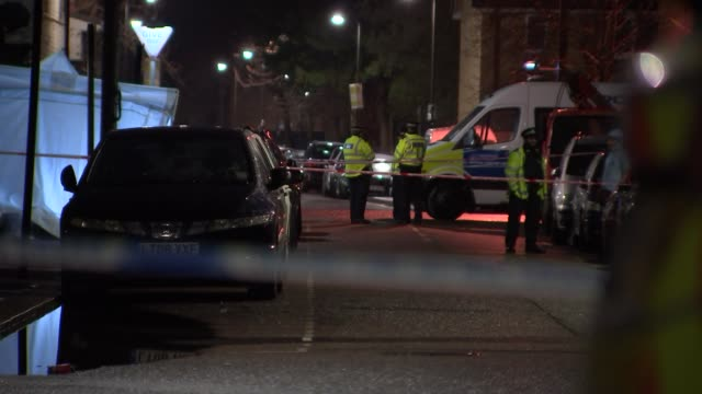 general views crime scene at night england london tottenham police car parked in front of blue police cordon tape at scene of shooting / white... - jumpsuit stock videos and b-roll footage