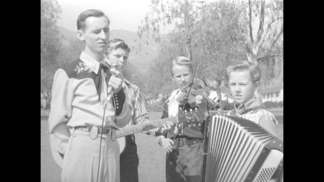 year-old robert plog stands outdoors with three child musicians - one with a guitar, one with a violin, one with a piano accordion; they wait for... - all shirts stock-videos und b-roll-filmmaterial