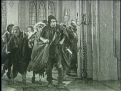 b/w 1800s angry crowd carrying weapons rounds corner + stops indoors - mob stock-videos und b-roll-filmmaterial