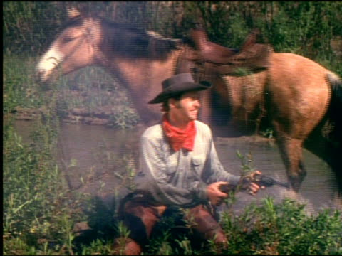 1800s cowboy standing by river shooting pistol is hit by bullet + falls down / horse walks away background - cowboy stock-videos und b-roll-filmmaterial