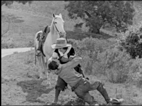 b/w 1800s cowgirl (texas guinan) fighting with man outdoors / horse in background - 19世紀風点の映像素材/bロール
