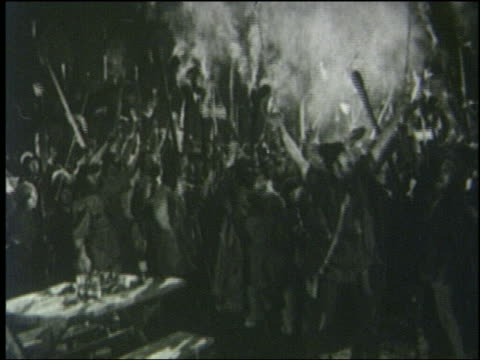 B/W 1800s crowd carrying weapons + torches shouts then starts to run at night