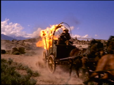 1800s PAN from cattle stampeding on plains to man driving speeding covered wagon on fire from Man In the Saddle
