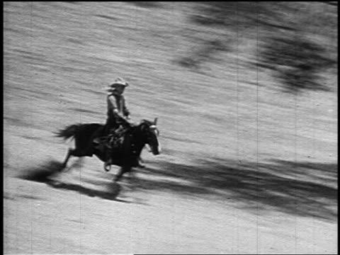 vídeos de stock, filmes e b-roll de b/w 1800s high angle tracking shot cowboy (william s. hart) riding running horse down hill on plain - estilo século dezenove