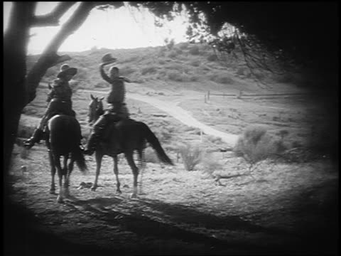 b/w 1800s rear view cowboy + cowgirl riding horses in countryside turn to wave + tip hat at camera - カウボーイ点の映像素材/bロール