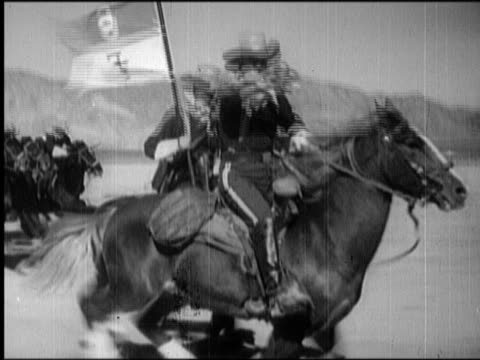 B/W 1800s tracking shot US Cavalry soldier blowing bugle while riding running horse / second man with flag in background