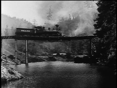 stockvideo's en b-roll-footage met b/w 1927 pan 1800s train crossing over burning bridge crashing into river below - 19e eeuwse stijl