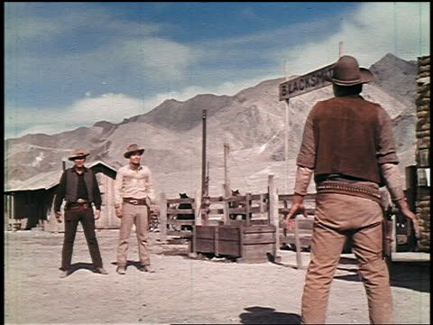 vidéos et rushes de 1800s two cowboys shooting + killing third cowboy in gunfight in town - film cinématographique