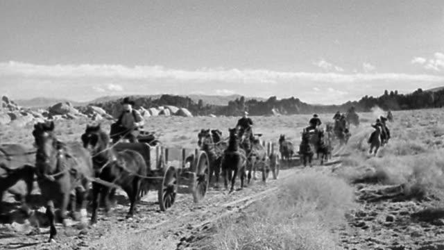 B/W 1800s wide shot horse-drawn wagons + horseback riders shooting guns speeding past camera in desert