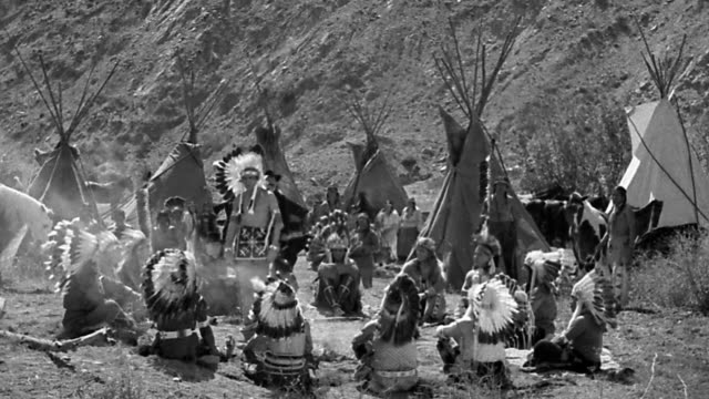 b/w 1800s wide shot native americans sitting in circle with man speaking + gesturing / teepees in background - cinematografi bildbanksvideor och videomaterial från bakom kulisserna