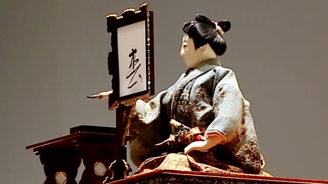 """year-old wind-up doll in kimono performed the """"kakizome"""" ritual january 2 japan--the first calligraphy writing of the new year. the male doll, its... - ドール点の映像素材/bロール"""