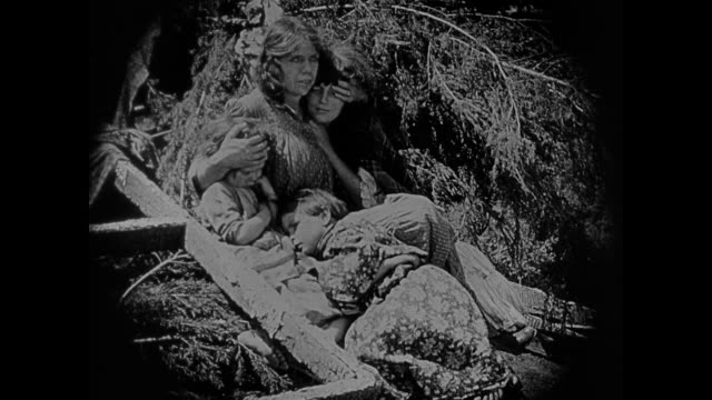 1860s A displaced family tries to find comfort on a hillside above the fighting armies