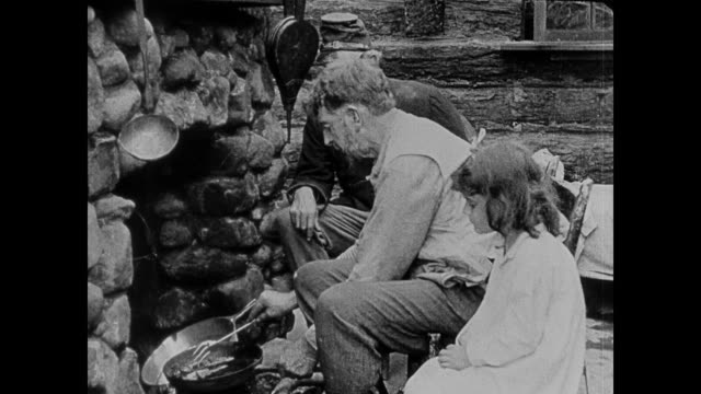 1860s a man cooks in log cabin while people come seeking help - poor family stock videos & royalty-free footage