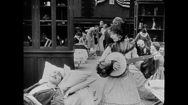 1860s an injured soldier (henry b. walhall) recognizes a volunteer (lillian gish), his crush from the photograph, when she performs for him in the hospital - banjo stock videos & royalty-free footage
