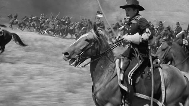 1870s reenactment US Cavalry officer (Errol Flynn) on horseback points saber, leads charge of men into battle