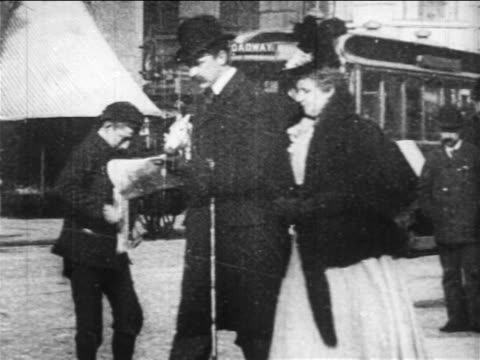 vídeos de stock e filmes b-roll de b/w 1890s slow motion paperboy selling newspapers to people on broadway sidewalk / nyc / newsreel - jornal