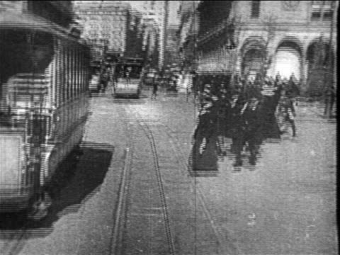 B/W 1890s trolley point of view on city street past pedestrians + other trolleys / NYC / newsreel