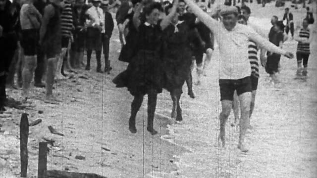 1890s wide shot couples performing cakewalk dances on beach / Coney Island