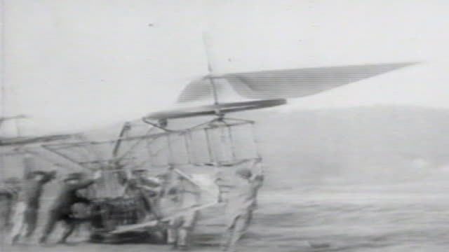 1900s b/w ws men try to control flying machine with spinning blades / united states - air vehicle stock videos & royalty-free footage