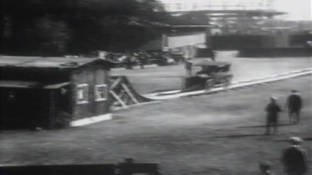 1900s b/w montage car goes down ramp and jumps over house / united states - stunt stock-videos und b-roll-filmmaterial