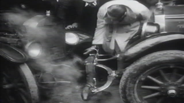 1900s b/w montage man drives his car into cement post / united states - 交通事故点の映像素材/bロール