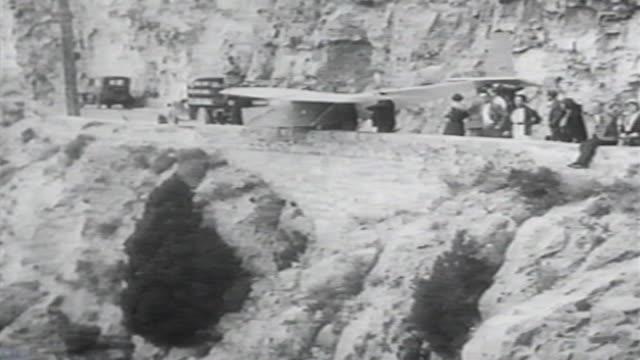 vídeos de stock e filmes b-roll de 1900s b/w montage man goes over cliff in glider and crashes / united states - acidente de avião