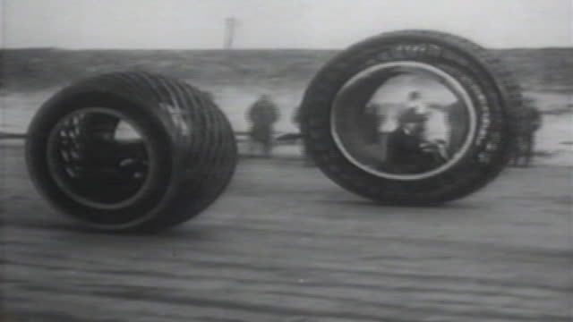 1900s b/w montage men drive large wheels / united states - erfindung stock-videos und b-roll-filmmaterial