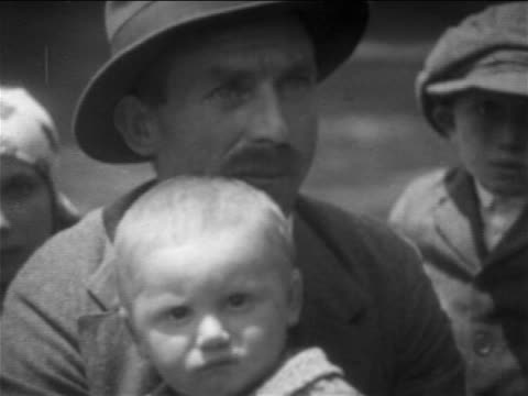 B/W 1900s close up PORTRAIT immigrant man in hat holding baby / NYC / newsreel