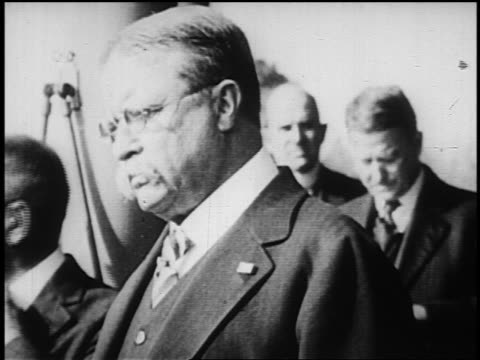 B/W 1900s close up Theodore Roosevelt surrounded by people talking to someone offscreen