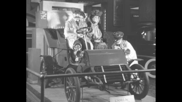vídeos de stock, filmes e b-roll de 1900s era vintage car with three moving mannequins and another in a duster coat turning the starter crank / note exact month/day not known - pano de pó
