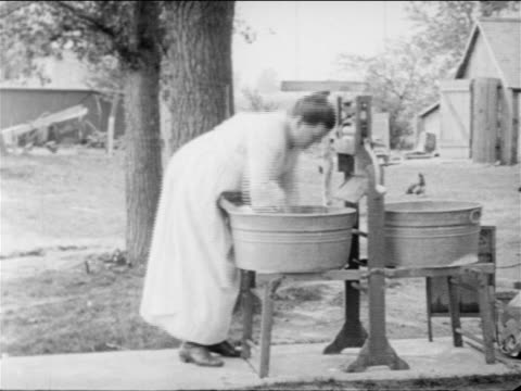 b/w 1900s farmwoman washing clothes in tub outdoors / documentary - stay at home mother stock videos & royalty-free footage