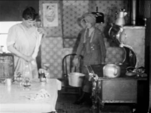 B/W 1900s girl in bonnet with pail entering kitchen where woman dries lamps / documentary