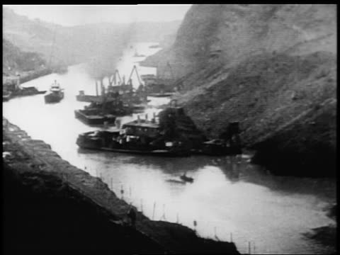 B/W 1900s high angle wide shot barges boats in Panama Canal / documentary