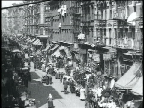 B/W 1900s high angle wide shot crowded city street with tenement buildings + pushcarts on Lower East Side / NYC