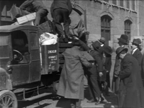B/W 1900s immigrant men loading truck with luggage / NYC / newsreel