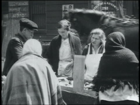 b/w 1900s immigrant women haggling with street vendor on lower east side / nyc - migration stock-videos und b-roll-filmmaterial