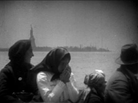 b/w 1900s immigrants on boat deck passing statue of liberty / one girl crying / newsreel - emigration and immigration点の映像素材/bロール