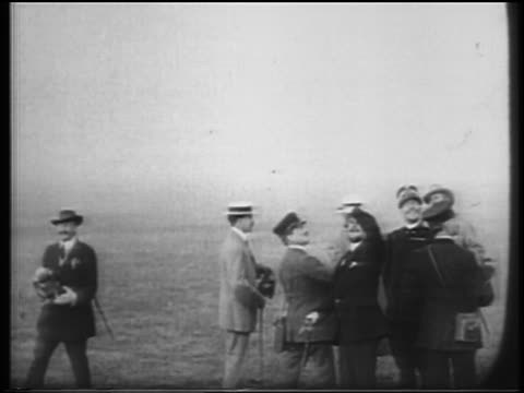 B/W 1900s men in hats looking up to watch Wright brothers flight / documentary