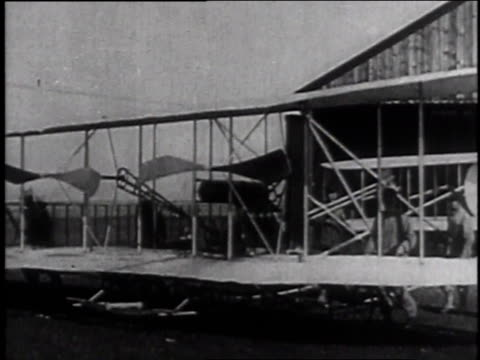 vídeos de stock, filmes e b-roll de 1900s ws men rolling out early creaky biplane from hanger to flightline / dayton ohio united states - orville wright