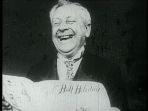 """vidéos et rushes de b/w 1900s middle-aged man (""""layman"""") reading newspaper + laughing uproariously - rire"""