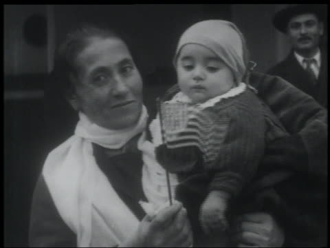B/W 1900s NEWSREEL close up immigrant woman holding baby waving small American flag talking