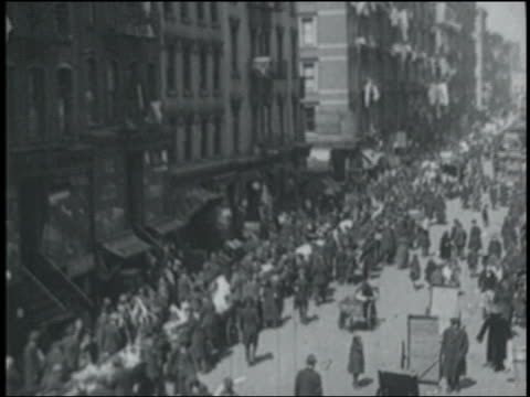 b/w 1900s newsreel high angle wide shot crowds on city street / nyc - immigrant stock videos & royalty-free footage