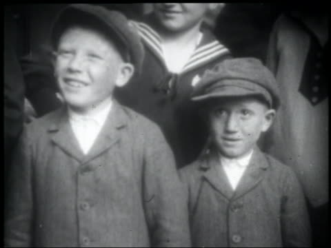 1900s newsreel two small immigrant boys wearing caps + looking up - solo bambini maschi video stock e b–roll