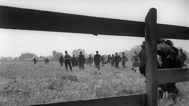 b/w 1900s rear view people climbing over fence + running across field towards airplane - 1940~1949年点の映像素材/bロール