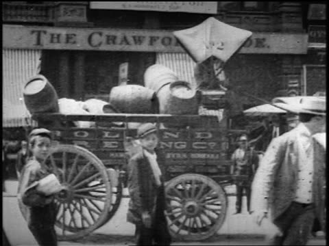 b/w 1900s slow motion traffic + horse-drawn carts on broadway in front of crawford shoe store - tram stock videos & royalty-free footage