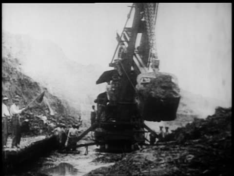 B/W 1900s steam shovel moving dirt in Panama Canal construction / documentary