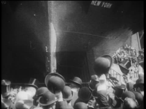 B/W 1900s woman smashing bottle on prow of Staten Island Ferry / crowd cheers as it pulls away