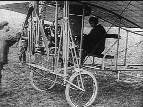 b/w 1900s/10s louis bleriot sitting in early airplane with man starting propeller engine - air vehicle stock videos & royalty-free footage