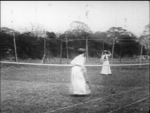 b/w 1900s/1910s 2 women playing tennis on grass court in hats + dresses - tennis stock videos & royalty-free footage